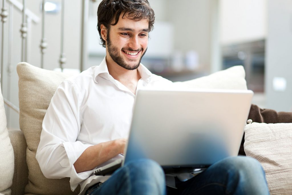 Doctor happily typing on laptop