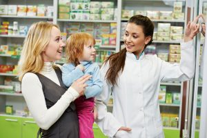 Pharmacist talking to mom and daughter