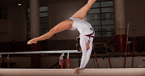 Gymnast tumbling on a balance beam