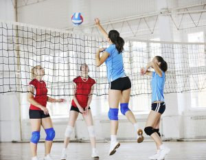 Volleyball player spiking at the net