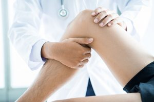 Doctor examining patient's knee injury